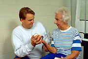 Trainer age 25 with woman age 80 using soup can weights at Lynnwood Recreation Center.  St Paul Minnesota USA