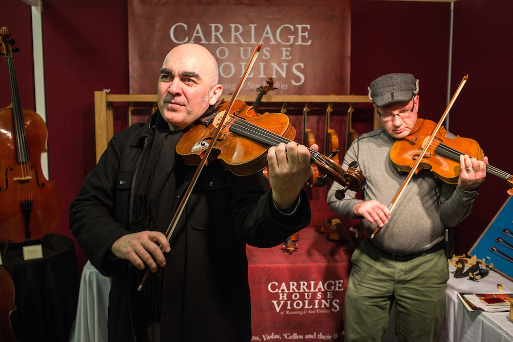 Visitors try instruments at Carriage House Violins, from Newton Upper Falls, Massachusetts.