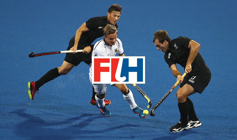 RIO DE JANEIRO, BRAZIL - AUGUST 14:  Mats Grambusch (C) of Germany is tackled by Simon Child (L) and Nic Woods during the Men's hockey quarter final match between the Germany and New Zealand on Day 9 of the Rio 2016 Olympic Games at the Olympic Hockey Centre on August 14, 2016 in Rio de Janeiro, Brazil.  (Photo by David Rogers/Getty Images)