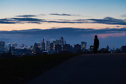 "A walker is seen against the backdrop of the city's pre-dawn skyline on Primrose Hill. The threatened snow from ""The Beast From The East"" weather system doesn't materialise overnight in London leaving a crisp, clear morning, seen from Primrose Hill in North London. London, February 27 2018."