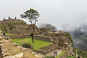 A group of tourists with local guide explore the Old ruins of  Machu Picchu, Cuzco, Peru