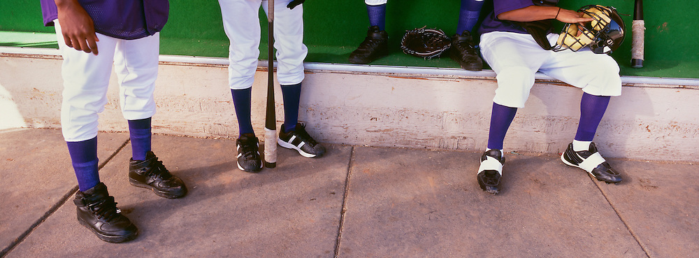 Low section of baseball player preparing for match in dugout