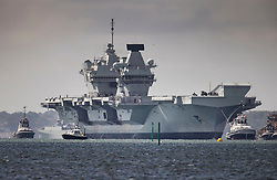© Licensed to London News Pictures. 02/07/2020. Portsmouth, UK. Royal Navy aircraft carrier HMS Queen Elizabeth is surrounded by tugs as she enters Portsmouth harbour. The 65,000 tonne supercarrier has been at sea for 10 weeks conducting trials of the new F35 Lightening fighter jets ahead of her first operational mission in 2021. Photo credit: Peter Macdiarmid/LNP