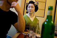 Miehina, a 20 year old maiko ( an apprentice geisha) from the Miyagawacho district of Kyoto, listening politely to one of her evening clients, in the tea house where she lives and works, Kyoto, Japan, Sunday, May 18th 2008.