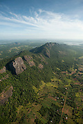 Aerial view over tanks, forest and paddy lands and mountain ridges.