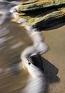 A close up view of rocks, pebbles, sand and crashing waves at the beautiful beach of Barcaggio in Corsica, France.