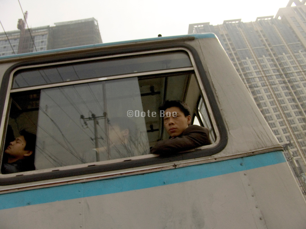 a boy looking out of the window of a riding public bus