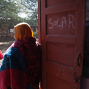 Women on the door of the solar energy engineer classroom, in the old campus of Barefoot College, in Tilonia (Rajasthan, India). Barefoot College, since 1989, has been harnessing the sun's energy to help rural communities, not just in Rajasthan. 01/2013 © Marida Augusto/Max Hirzel