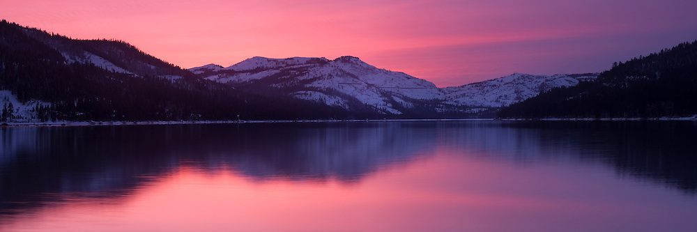 A photo of a pink alpenglow sunset reflecting on Donner Lake in winter near Lake Tahoe in California