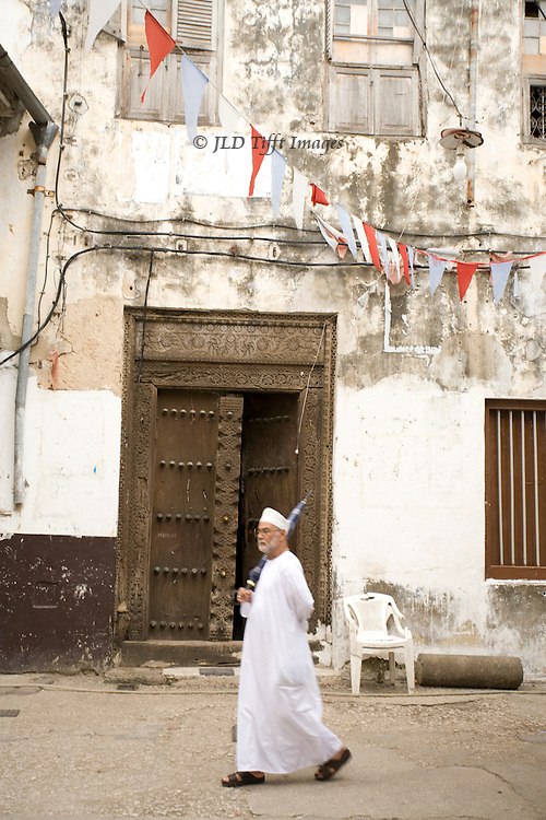 Stonetown, man wearing white disdasha strides past a traditionally carved wooden door