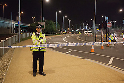 © licensed to London News Pictures. London, UK 01/08/2012. A cyclist was struck by an official Olympic bus and died at the scene, which is at the junction of the Eastway and the A12 East Cross Route, close to the northwestern corner of the Olympic Park at around 7.40pm on 01/08/12. A police officer protects the police line of the crime scene.  Photo credit: Tolga Akmen/LNP