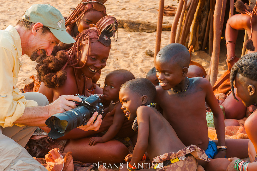 Visitor to Himba camp showing photo to   Himba boy, Kaokoland, Namibia