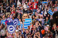 Audience members hold signs and flags as President Barack Obama speaks at the Democratic National Convention on Thursday, September 6, 2012 in Charlotte, NC.