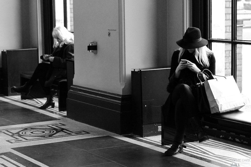 A very elegant woman busy on her iPhone at the V&A Museum in London's South Kensington