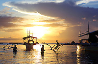 Fishermen on outrigger fishing boat at sunset.