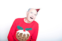 Senior adult man wearing a Christmas jumper and a red party hat