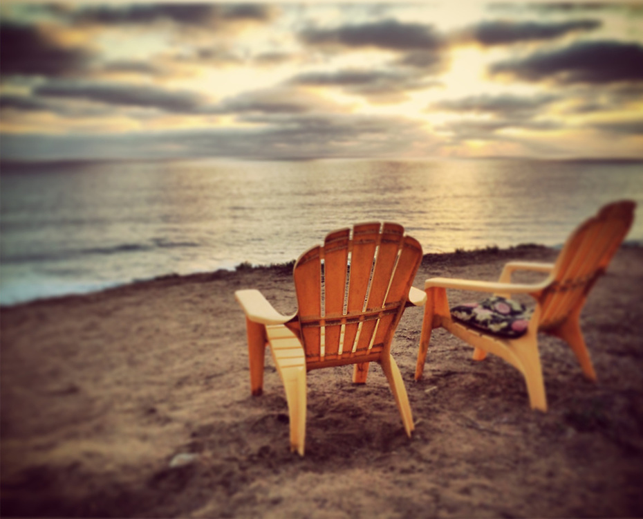 Empty chairs facing ocean at sunset in Del Mar, CA