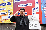 """A Japanese man dressed at North Korean Dictator, Kim Jong Un holds s sigh celebrating the naming of the new Reiwa Era in Shinjuku, Tokyo, Japan. Monday April 1st 2019. The Reiwa era officially starts on May 1st when Crown Prince Naruhito will assume the thrown following the abdication of his father, Emperor Akihito. The two Chinese characters making-up the new name, known as a  gengo, translate roughly to """"good fortune"""" and """"peace"""" or """"harmony""""."""