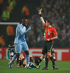 MANCHESTER, ENGLAND - Thursday, March 15, 2012: Manchester City's Yaya Toure is shown the yellow card by referee Tom Harald Hagen during the UEFA Europa League Round of 16 2nd Leg match against Sporting Clube de Portugal at City of Manchester Stadium. (Pic by David Rawcliffe/Propaganda)