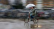 Een meisje op een vouwfiets rijdt met een paraplu boven haar hoofd en een aan haar stuur door de stromende regen over het Jaarbeursplein in Utrecht
