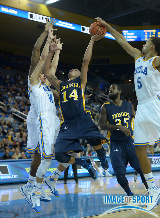 Nov 8, 2013; Los Angeles, CA, USA; UCLA players Tony Parker (23), Zach LaVine (14) and Kyle Anderson (5) defend Drexel Dragons guard Damion Lee (14) at Pauley Pavilion. UCLA defeated Drexel 72-67.