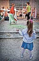 """Gente del pubblico viene coinvolta a ballare con una ballerina del gruppo musicale di Pizzica """"Arakne Mediterranea"""" davanti ad una piccola spettatrice durante un concerto a """"Castello Monaci"""" nei pressi di Salice Salentino in provincia di Lecce. 30/05/2010 (PH Gabriele Spedicato)..People dancing with the dancers of """"Arakne Mediterranea"""" during the concert in """"Castello Monaci"""" near Salice Salentino, a Town in province of Lecce. 30/05/2010 PH Gabriele Spedicato..La pizzica, o, detta nella sua forma più tradizionale pizzica pizzica, è una danza popolare attribuita oggi particolarmente al Salento, ma in realtà era praticata sino agli anni '70 del XX sec. in tutta la Puglia centro-meridionale e in Basilicata..Fa parte della grande famiglia delle tarantelle, come si usa chiamare quel variegato gruppo di danze diffuse dall'Età Moderna nell'Italia meridionale"""