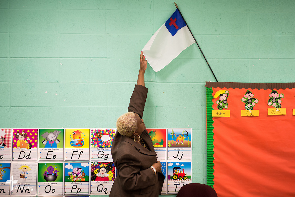 Preschool teacher Victoria Richardson adjusts the Christian flag at the beginning of classes at Trinity Evangelical Lutheran School on Monday, April 7, 2014, in Mobile, Ala. LCMS Communications/Erik M. Lunsford
