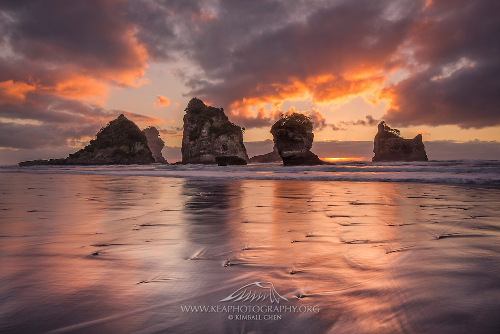 The sun sets behind the sea stacks, while reflecting its glow onto Motukiekie Beach, along the West Coast of New Zealand.