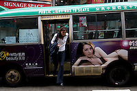 A young insurance company executive gets off a mini bus in Central district, Hong Kong 2009.