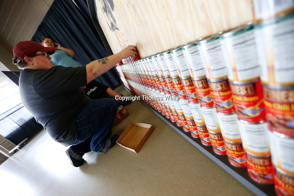 Thomas Wells | BUY at PHOTOS.DJOURNAL.COM<br /> Lou Patterson from Asurion lines up another row of cans with the red label out to help form an American flag as their entry for the United Way food sculptor competetion.