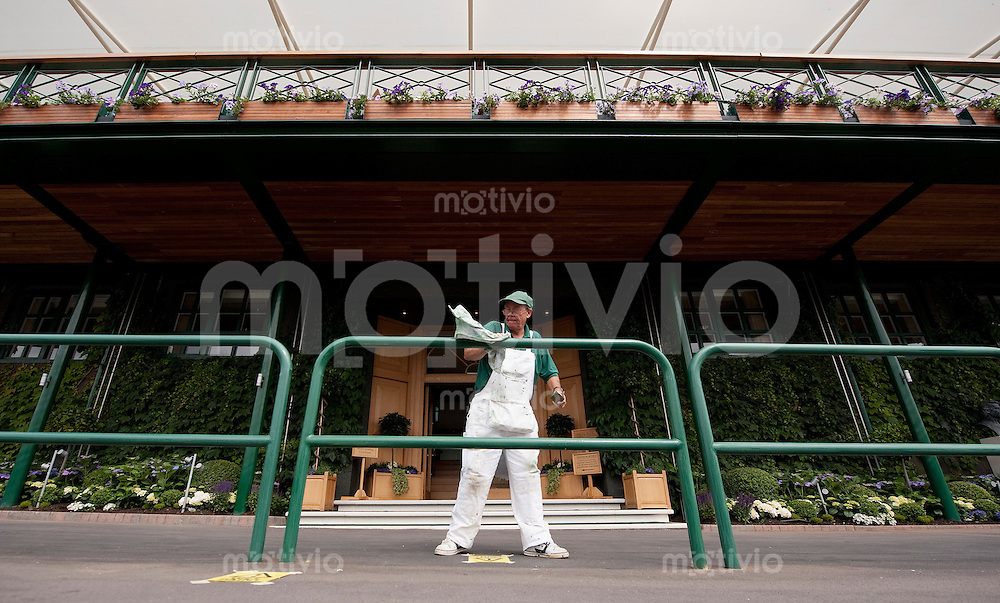 A painter works on the balustrade in front of the Club House Entrance of Center Court. Preparation for The Wimbledon Championships 2010 The All England Lawn Tennis & Croquet Club  Sunday Pre Championships Sunday 20/06/2010
