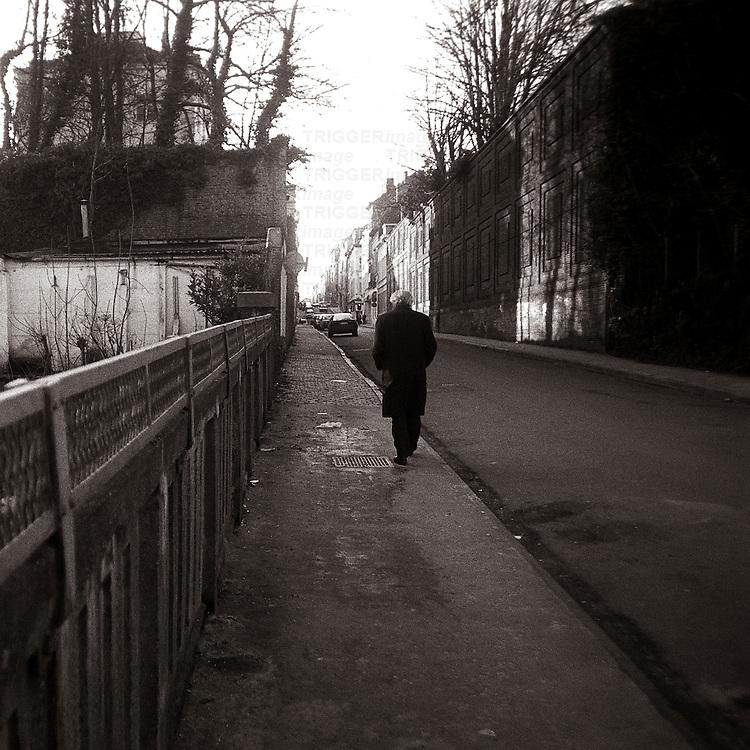 An old man walking along a deserted street