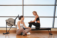 Two women talking at rowing machine in health club