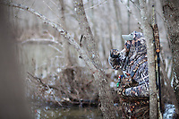DUCK HUNTER WEARING REALTREE MAX 4 CAMOUFLAGE CALLING DUCKS FROM FLOODED TIMBER