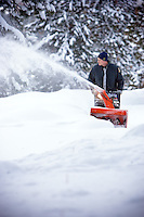 JEROME A. POLLOS/Press..Coeur d'Alene firefighter Tom Hiltenbrand navigates a snowblower Wednesday along the half-mile long road leading to the home of Don and Aletha Dunn.
