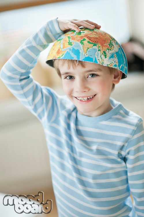 Portrait of young boy with world map as bowl on his head