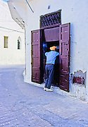 AFRICA; MOROCCO; TANGIER:  Typical street scene in the kasbah of Tangier with man in turban shopping at small storefront.