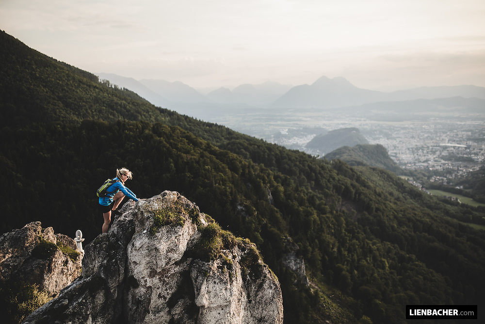 young woman climbs the Nockstein at sunset, overlooking the City of Salzburg