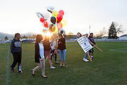 On May 2, 2014, students and friends of slain German exchange student, Diren Dede, carry balloons on to the soccer field at Fort Missoula where Dede played soccer. Dede wore jersey #4 when playing soccer. In a black sweater with pink letters is Leslie Wozniak, a neighbor of Markus Kaarma who is accused of shooting and killing Dede in his garage on April 27, 2014. Wozniak helped organize the vigil.