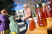Lee Knight, center, sells Lee Family Honey to Melisa Nielsen during the final Farmers Market of the year at Pioneer Park in downtown Salt Lake City, Saturday, Oct. 27, 2012.
