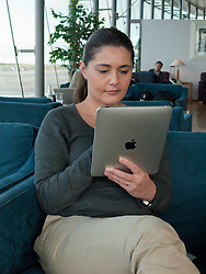 Woman using iPad computer tablet in airport departure lounge
