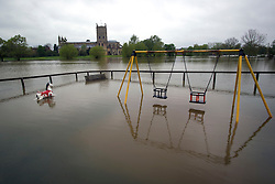 © London News Pictures. 01/05/2012. Tewkesbury, UK. A flooded childs playground in front of Abbey Church of St Mary the Virgin inTewkesbury, Gloucestershire, England on May 1, 2012. The UK has had its wettest April in over a century, with some areas seeing three times their usual average rainfall, according to figures from the Met Office. Photo credit : Ben Cawthra /LNP