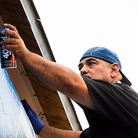 Giovanni Nez paints a mural in remembrance of his son along Route 66 in Gallup on Friday.