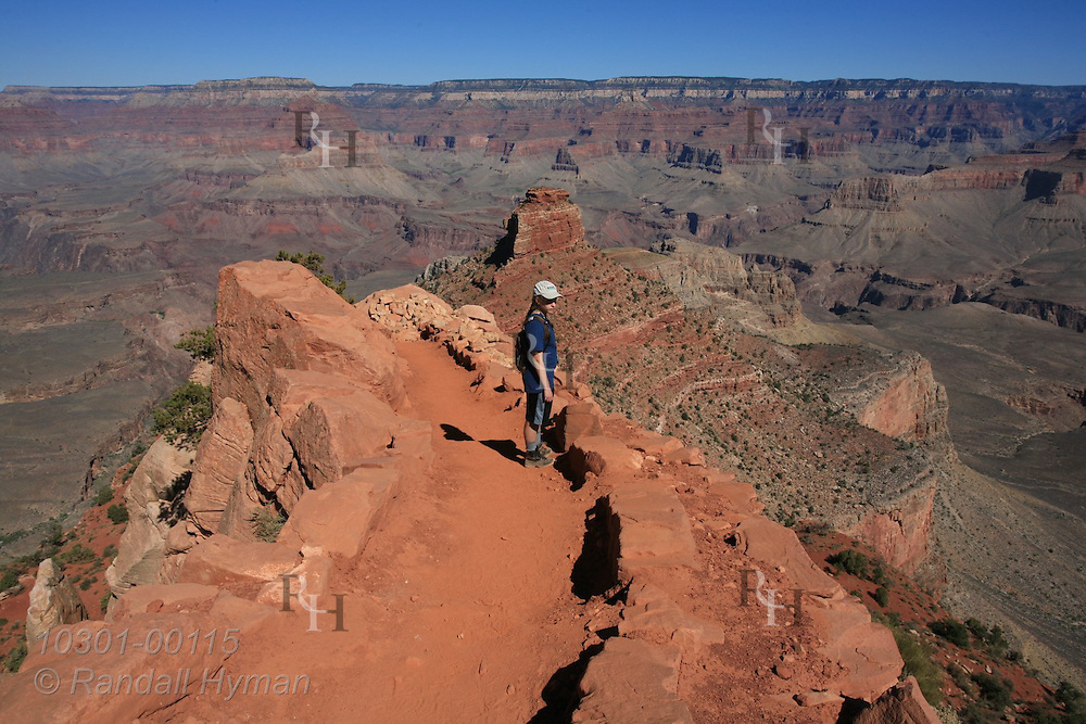 Girl hikes down South Kaibab Trail in the red dirt of the Hermit Formation above O'Neill Butte and Tonto Platform; Grand Canyon National Park, Arizona.