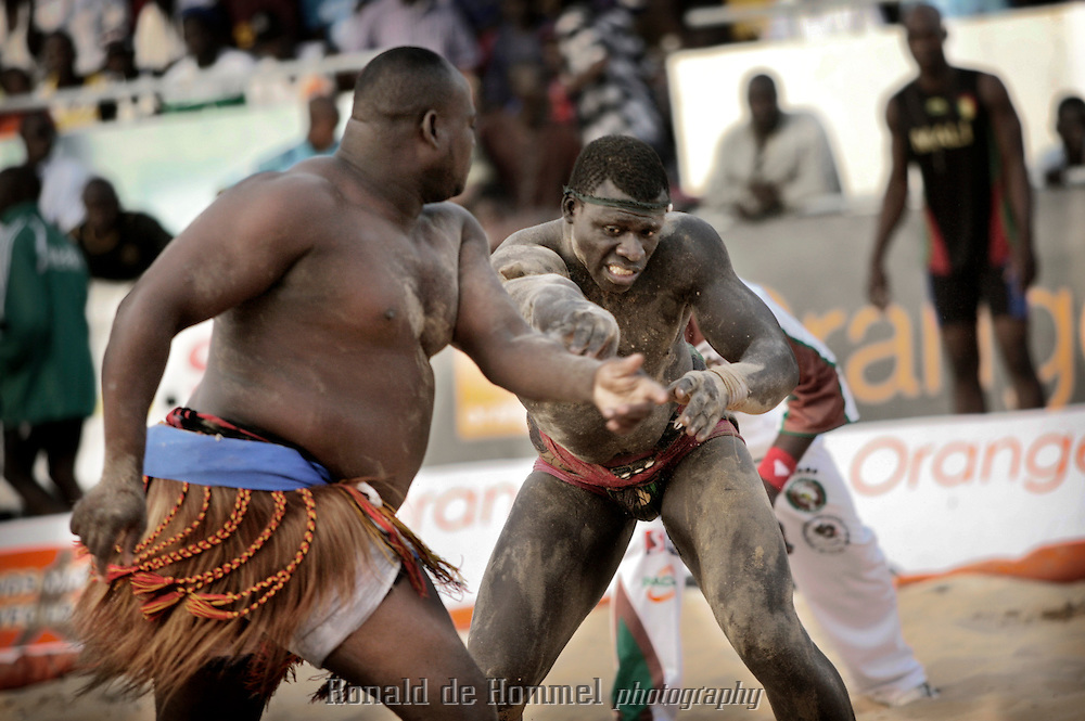 African traditional wrestlers during the international championship of The Economic Community Of West African States (ECOWAS or CEDEAO) in Dakar Senegal. After losing the title to Nigeria last year, the Senegalese home team came out as champion again this time. The championship is prestigious, but commercial wrestling where the fighters are allowed to punch (lutte avec frappe) is more popular with audience and players. The prize money in those fights goes up to 150.000 Euros. The matches attract up to 60.000 spectators. Wrestling has become more popular than football in Senegal in recent years.