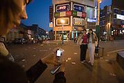 Hongdae. Girls taking souvenir photos at dusk.