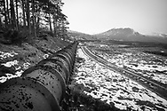 This pipeline brings water down the valley from high up on the Allt na Glaic Moire river to drain into Loch Droma, an artificial loch formed by a dam, in the Scottish Highlands near Ullapool.