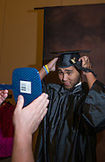 Even Richard fixes his cap before getting his Graduation portrait taken during the Grad Fair in the Baker Ballroom.