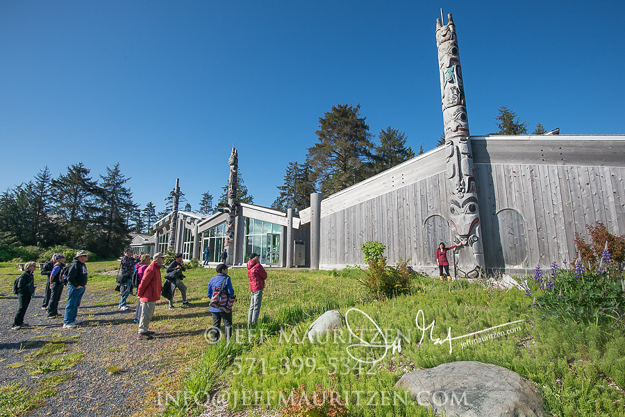 A guide explains the symbols on the Haida totem poles to visitors at the Heritage Centre at Skidegate, Graham Island, British Columbia, Canada.
