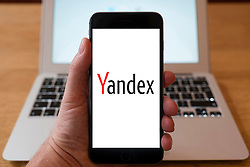 Using iPhone smartphone to display logo of Yandex, a Russian multinational technology company specializing in Internet-related services